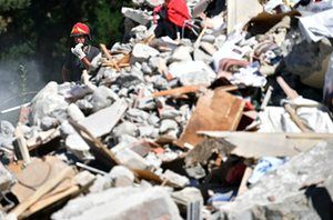 Emergency workers search the rubble of a building that was destroyed during an earthquake yesterday morning in Amatrice, Italy