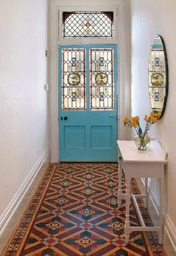 Turquoise blue painted front door with decorative / patterned tile floor…