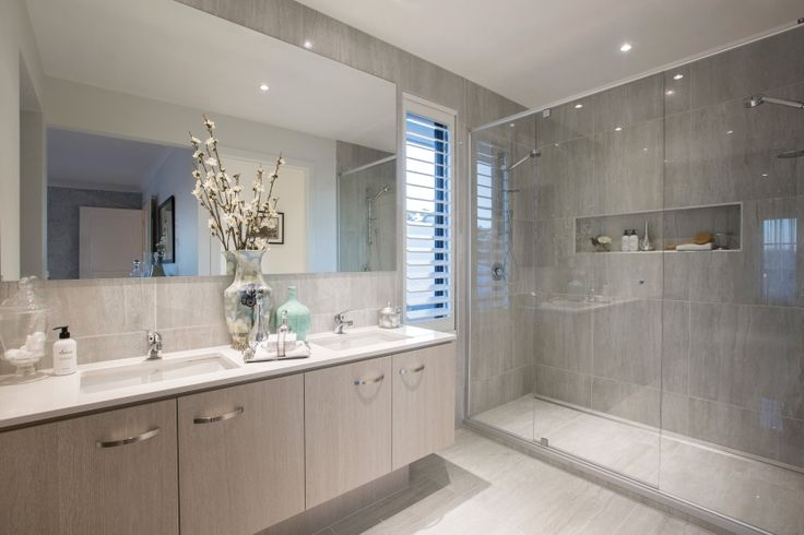 A neutral base palette of grey tiles and warm timber cabinetry convey the Champagne France theme. Double shower heads and recessed shower shelving bring the functionality to this gorgeous bathroom.