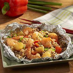 Fideos Ramen con Camarones y Salsa Teriyaki a la Parrilla: Camarones, fideos ramen, pimiento rojo, trozos de piña y salsa teriyaki mezclados y cocinados en un paquete de papel de aluminio a la parilla