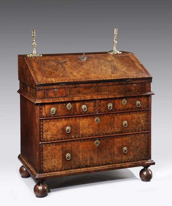 An excellent Queen Anne period walnut veneered bureau. A transitional piece made in two parts, retaining its original locks and penny ring handles, and raised on bun feet. Circa 1705.      Bureaus saw a decline in fashion during the eighties and nineties, their angled fall unable to enclose large computers. With the advent of portable laptops and ipads, these pieces of furniture remain excellent value for money and extremely useful and compact objects.