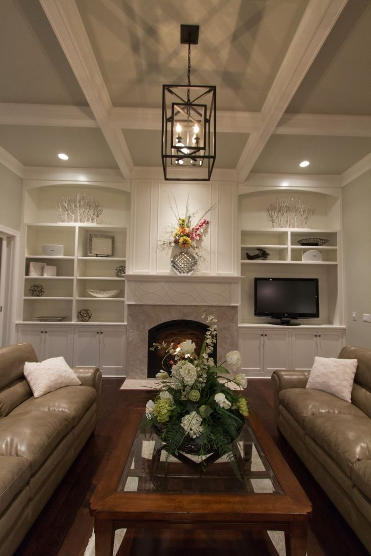 Great Room With Box Beam Ceiling And Cabinets Flanking The