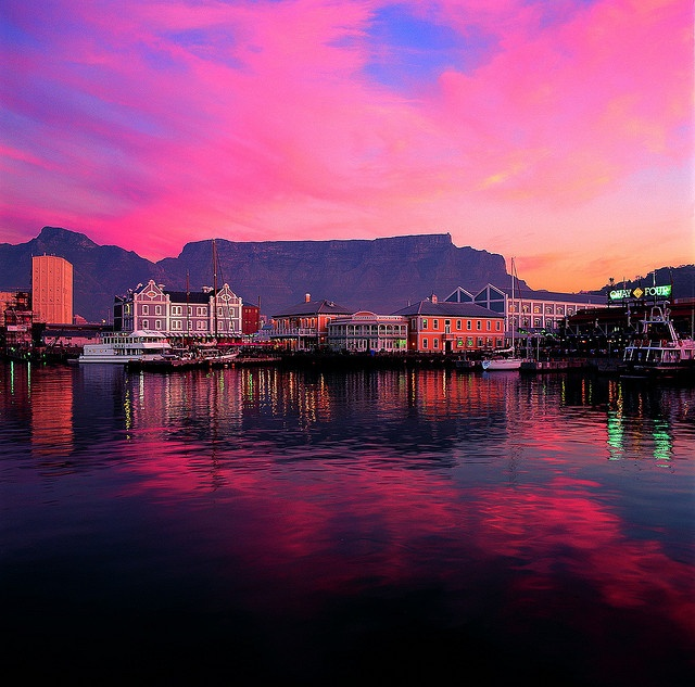 A landscape shot of The Table Bay Hotel on the left, with an exquisite shot of Table Mountain at sunset.