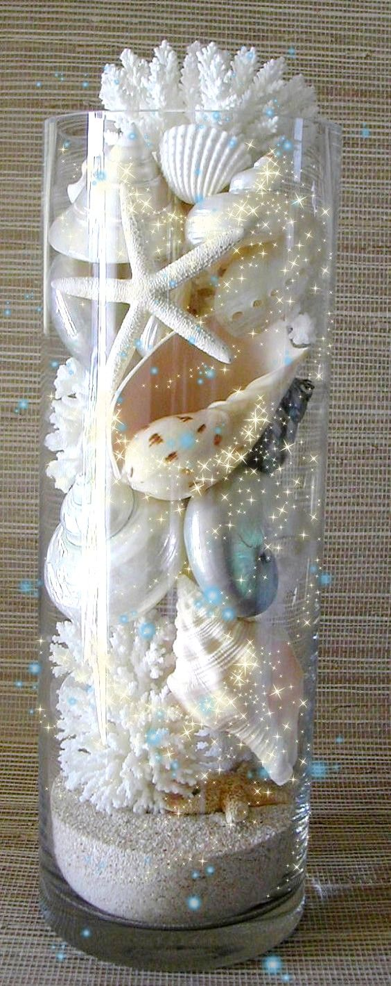 Pretty glass container filled with shells and sand