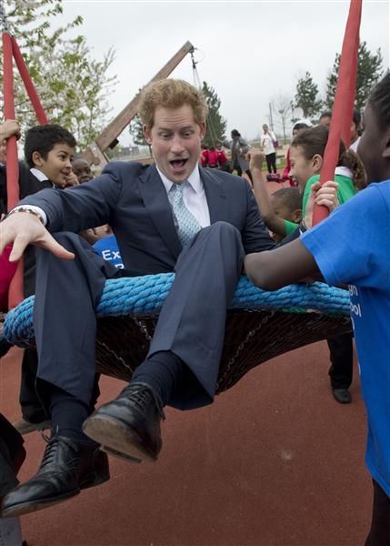 Prince Harry is pushed on a swing by children from Gainsborough Primary School as he visits the redeveloped Queen Elizabeth Olympic Park in London on 04.04.14