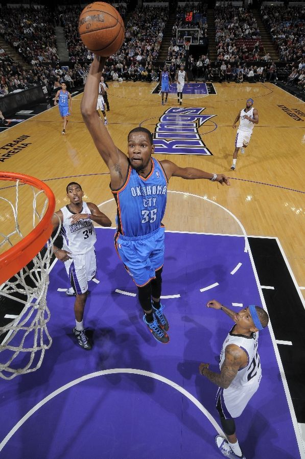 Kevin Durant #35 of the Oklahoma City Thunder rises for a dunk against Jason Thompson #34 and Isaiah Thomas #22