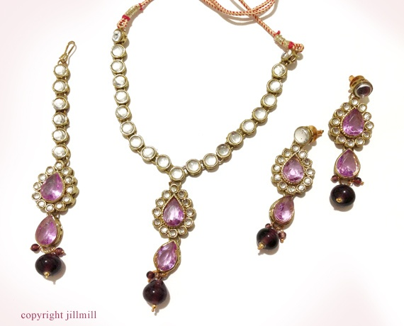 This set of white Kundans and mauve stones bring a ladylike charm to any outfit.