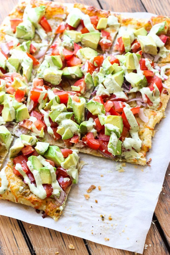 Skinny Avocado Pizza - Topped with avocados, tomatoes, red onion, cheeses, zesty pesto, with a blend of garlic, cilantro and avocado drizzled over the top. Yum!