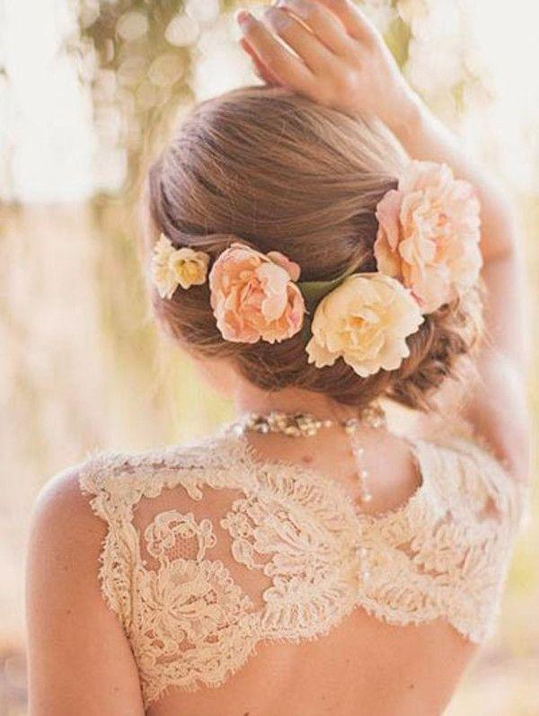 Pettinatura da sposa con capelli raccolti bassi e fiori freschi.