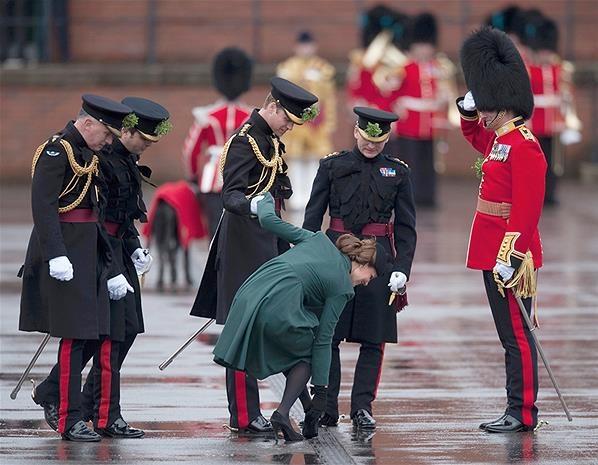 Le Prince William soutient sa femme, Kate Middleton, pendant qu'elle tente de décoincer son talon aiguille, bloqué dans une grille. (© REUTERS/Kieran Doherty)    Pour les sols compliqués, évitez les talons aiguilles, pensez à www.Shoette.com