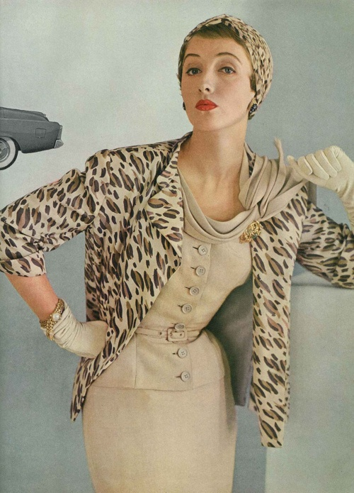 Model in a beige silk suit by Adele Style - many buttons, drapey collar. Simpson, available at B. Altman & Co. Ph by John Rawlings, Vogue, February 1953
