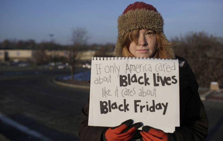 A demonstrator protesting the shooting death of Michael Brown holds a sign near the entrance to a local Wal-Mart store on Black Friday in Ferguson, Missouri