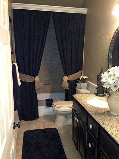 Like the idea of two different shower curtains pulled back by burlap ties. And the extra touch that covers up the shower rack
