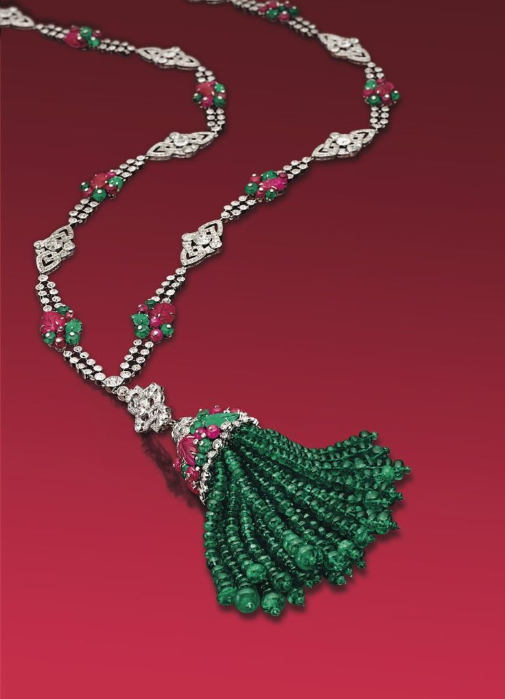 AN ART DECO DIAMOND, EMERALD AND RUBY SAUTOIR, BY BOUCHERON Suspending a detachable emerald bead tassel, the cap set with carved ruby and emeralds of foliate motif, enhanced with emerald and ruby beads, trimmed with old European-cut diamonds, from an openwork circular-cut diamond surmount, to the two-row old European-cut diamond necklace, intersected by openwork old European-cut diamond openwork links and plaques set with carved rubies and emeralds interspersed with emerald and ruby beads…