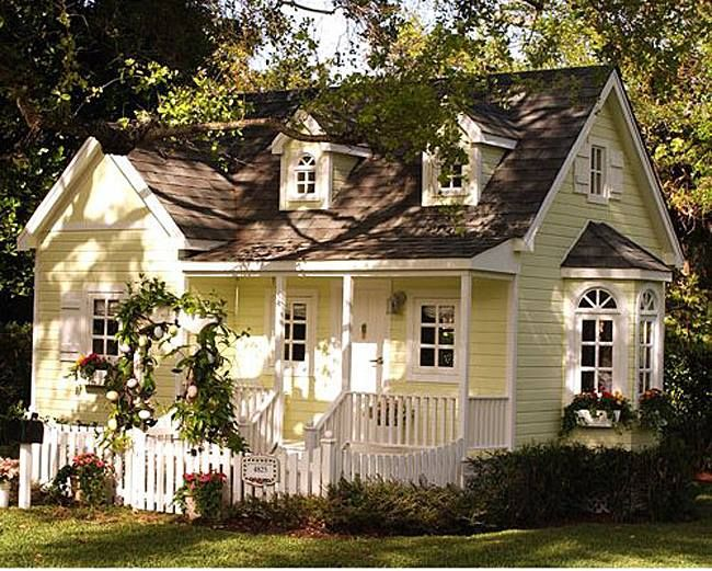 A yellow house with a white-trimmed porch and an arbor! Perfection!