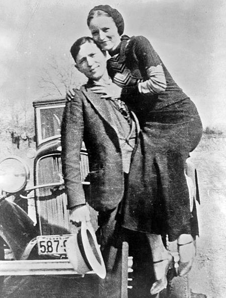 "Photo: Bonnie Parker and Clyde Barrow, sometime between 1932 and 1934, posing in front of a 1932 Ford V-8 automobile. Credit: Library of Congress, Prints and Photographs Division. Read more on the GenealogyBank blog: ""Violent End to Bonnie and Clyde's Life of Crime"" https://blog.genealogybank.com/violent-end-to-bonnie-and-clydes-life-of-crime.html"