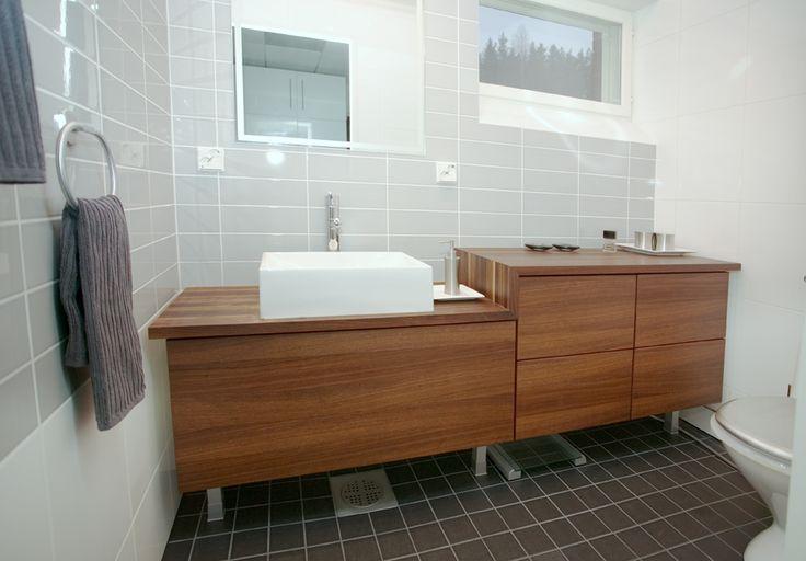 Kylpyhuoneen kaapisto, jonka vetolaatikot avautuvat huomaamattomista sormiurista vetämällä ja vetimiä ei tarvita. Vahattu tiikkiviilu on erittäin kestävä materiaali. #puuvaja