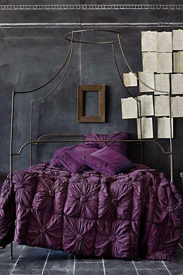 Du violet et une peinture gris anthracite pour une chambre, c'est décidément chic  ! Pour la déco de cette chambre, le gris des murs est obtenu avec une peinture à tableau noir, la frise du haut est dessinée à la craie et l'effet de tableau d'école essuyé est réalisé à l'éponge. Le tout est fixé au vernis mat incolore. Le lit à baldaquin en fer forgé et le couvre-lit en satin violet donnent le style baroque à cette chambre d'adulte.