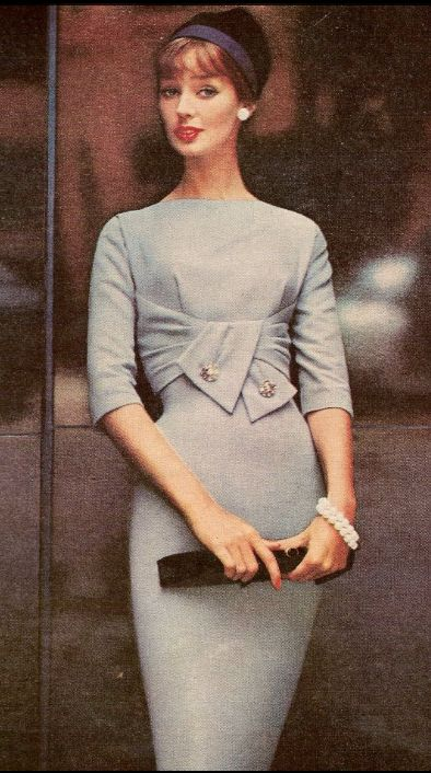 1958 Dolores Hawkins wearing an empire draped wool dress by R & K Originals, hat by John Frederics grey blue wool sheath dress shelf bust tie front brooch pins 3/4 sleeves high boatneck color photo print ad model magazine vintage fashion