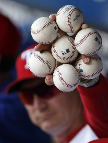 Texas Rangers manager Jeff Banister holds up 7 baseballs with one hand before a game against the Detroit Tigers at Globe Life Park in Arlington on Tuesday, September 29, 2015. (Vernon Bryant/The Dallas Morning News)