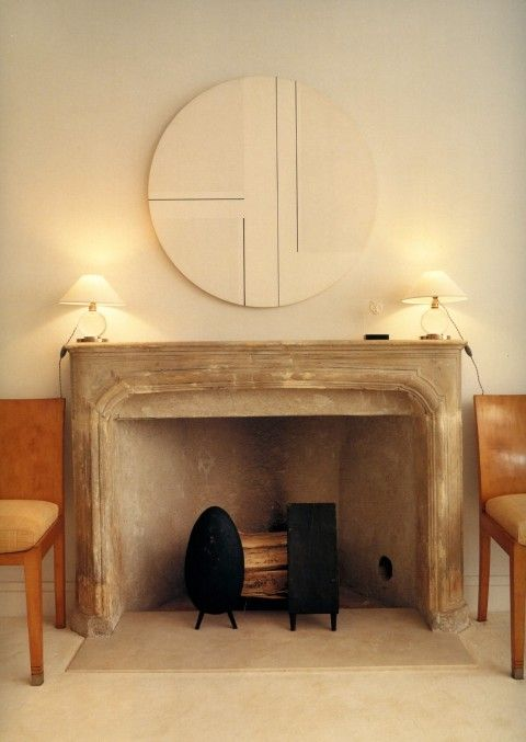 a classic combination of (very) old and new with a vintage French limestone mantel and clean, modern furnishings in a neutral scheme