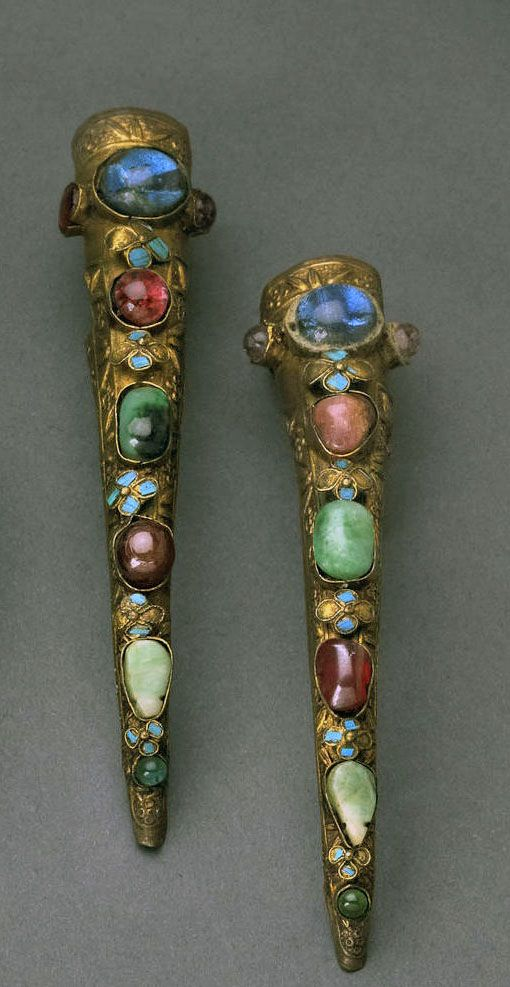 Nail covers, China, Late Qing Dynasty. Gilt-washed, metal mounted with coloured glass and jade cabochons, separated by tiny flowers covered in kingfisher feathers