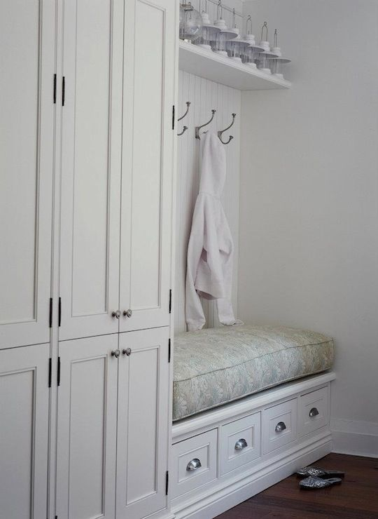 Fantastic mudroom with built-in locker storage. White raised panel mud room cabinet doors and built-in mudroom bench with beadboard backsplash. Mudroom bench with floral bench cushion and wall hooks.