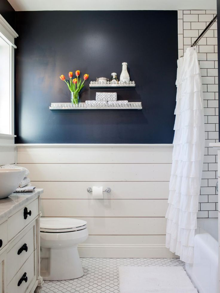 Master Bath, AFTER Chip and Joanna reconfigured and opened up the bathroom, stealing space from an adjacent linen closet. They also gave it a whole new look with painted shiplap, white subway tile and rich navy wall paint.