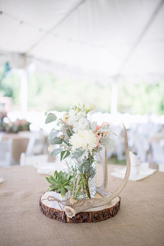 Elegant and rustic summer wedding centerpiece with a log slice and antler decoration