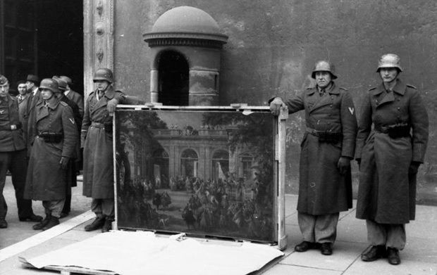 German soldiers of the Hemann Goring Division pose in front of Palazzo Venezia in Rome in 1944 with a picture taken from the Biblioteca del Museo Nazionale de Napoll before the Allied forced arrival.