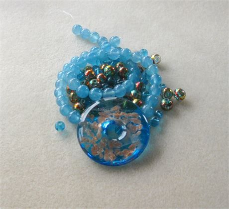 These DIY jewelry kits contain a pendant with coordinating beads and findings so you can easily make a necklace with one stop shopping!    *  blue lampwork glass donut pendant with copper accents, NOT DRILLED, 40mm   *  blue jade round beads, 15 strand, 8mm   *  AB blue glass round beads, 8mm   *  Czech blue glass beads, 6mm   *  antiqued copper spacers, 4mm   *  antiqued copper designer toggle clasp, 14mm   Each kit comes with 4 crimp beads and 20 inches of beadalon stringing wire. You…