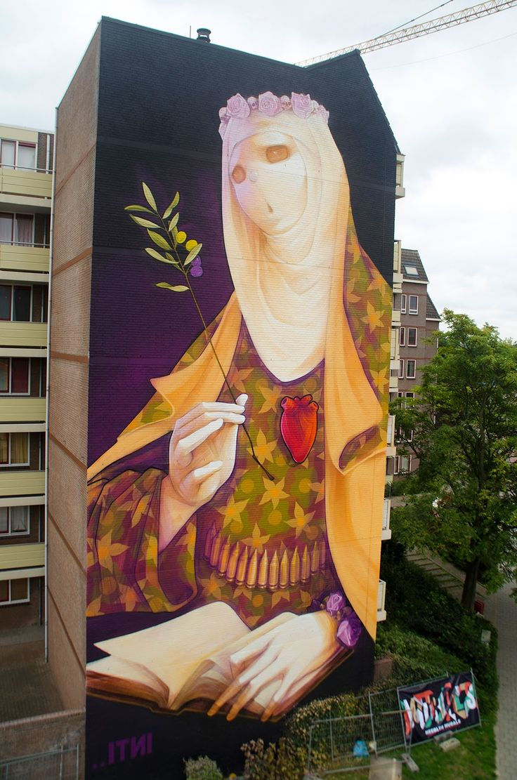 """INTI """"Creed""""  For HRLN 2014 - Heerlen, Netherlands ~ Entitiled """"Creed"""", the Chilean muralist painted this massive artwork which shows one of his recurring Virgins holding an Olive branch and dressed up with a camo-inspired outfit combined with a bullet belt. Peace and War."""