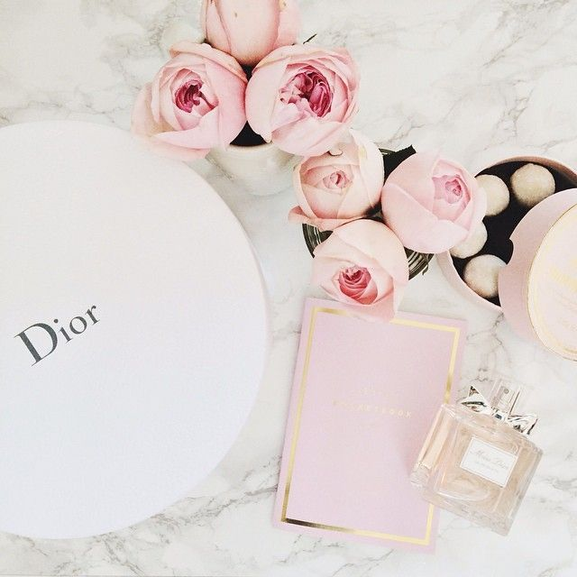 Dior, perfume, and a pile of flowers.