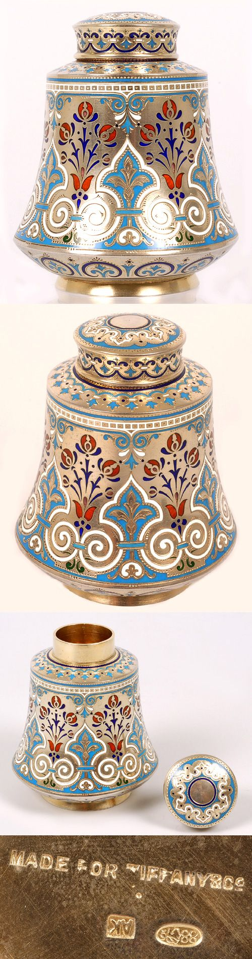 A Russian silver gilt and champleve enamel tea caddy by Antip Kuzmichev, Moscow, Circa 1896-1908. Of cylindrical shape with flaring sides, raised on a circular base, the caddy is worked in multi-color scrolling and foliate motifs using predominately turquoise, white, red and cobalt enamel. The slightly domed lid is similarly decorated.