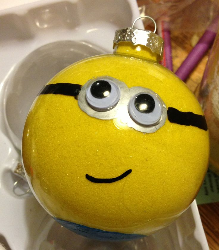 Clear glass ornament, pledge floor care finish, craft sand, acrylic paint or paint markers and of course googly eye= cutest diy minion ornament