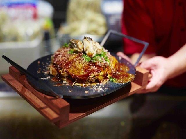 《 大崎 》『TAKASAGOMARU』の「TAKASAGO スペシャル肉玉 そば or うどん」  編集部 船山壮太選  大崎  編集部最寄の大崎駅に、今年突如誕生した商業施設「パークシティ大崎 オリーブテラス」の中にある店舗。   広島に2店舗を構えるお好み焼きとワインの店『TAKASAGOMARU』が東京に初上陸。広島の製麺所で作る自家製麺や、鰹、煮干し、昆布、椎茸をブレンドした出汁を軸にした、本場の味が楽しめる。自家製麺は蒸しているため、もちもちの食感。抑えて圧縮させるのではなく、ふんわりと仕上げ、最後にオタフクソースをかける。   人気の「TAKASAGO スペシャル肉玉 そば or うどん」は、広島特産のカキ、エビ、イカ、タコが入ったボリュームのある逸品。魚介のダシも加わり、えも言われぬ味わいに。どっしりとした味わいの「お好み焼きワイン」と合わせれば、その相性に唸るはず。ちなみに、黒田選手などのサイン入りユニフォームなどが飾られたカープ女子悶絶のカープ部屋(赤を基調にしている)もあり。