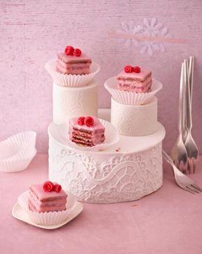 Die köstlichen Petit Fours werden mit rosa Zuckerguss und roten Marzipanrosen verziert.