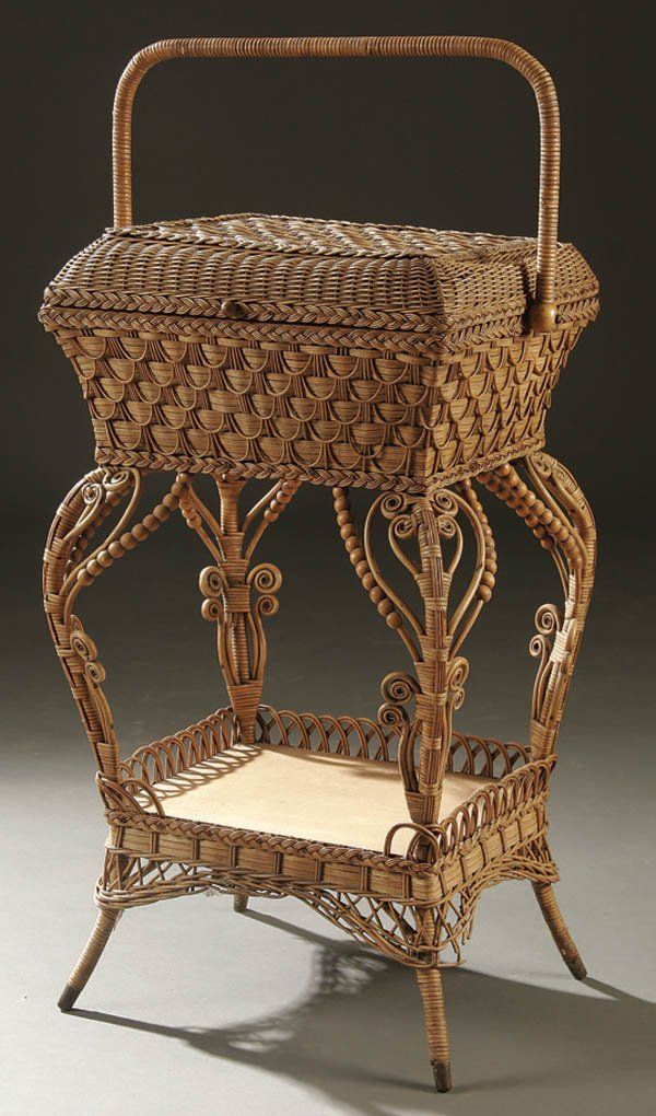 A VICTORIAN WICKER SEWING BASKET circa 1900 with scrolled decoration on 4 legs.