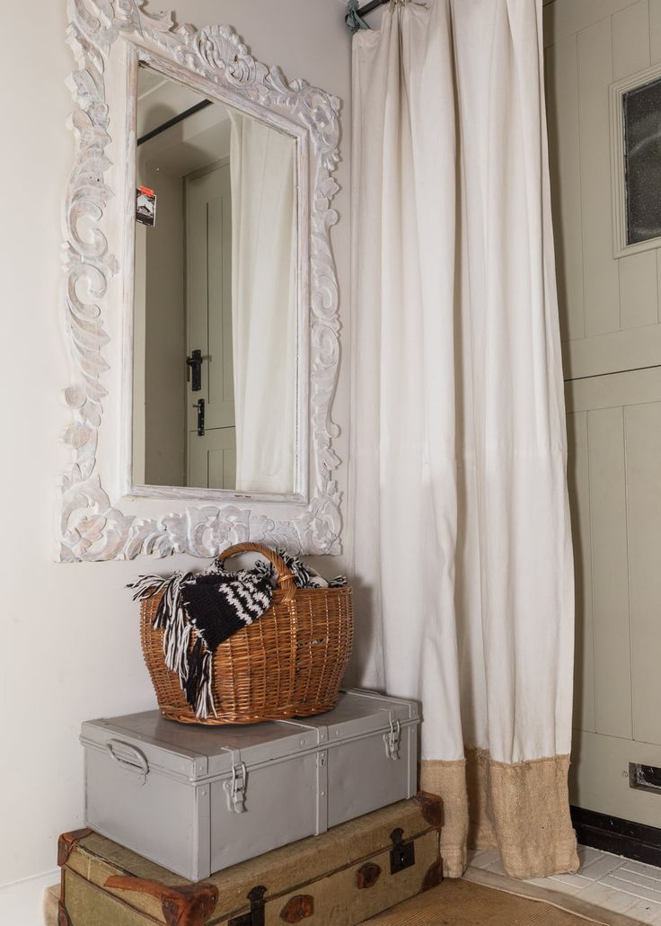 Old trunks and a basket provide handy storage by the front door.