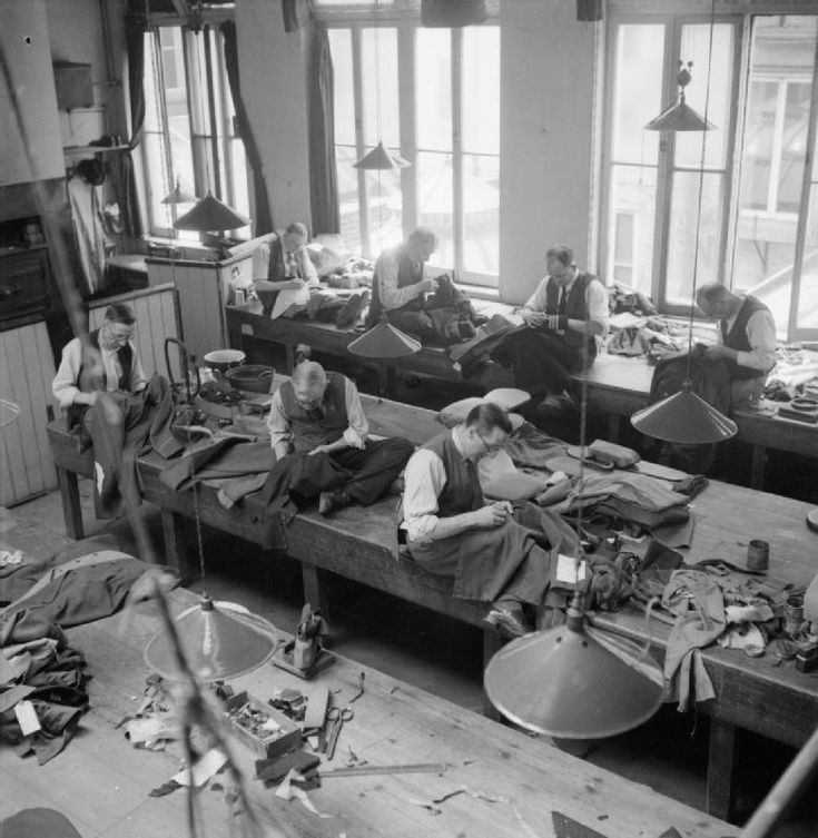 A view of the workroom at Henry Poole and Co. located on Savile Row London showing tailors at work on various types of jacket, including a naval officer's jacket. (1944)
