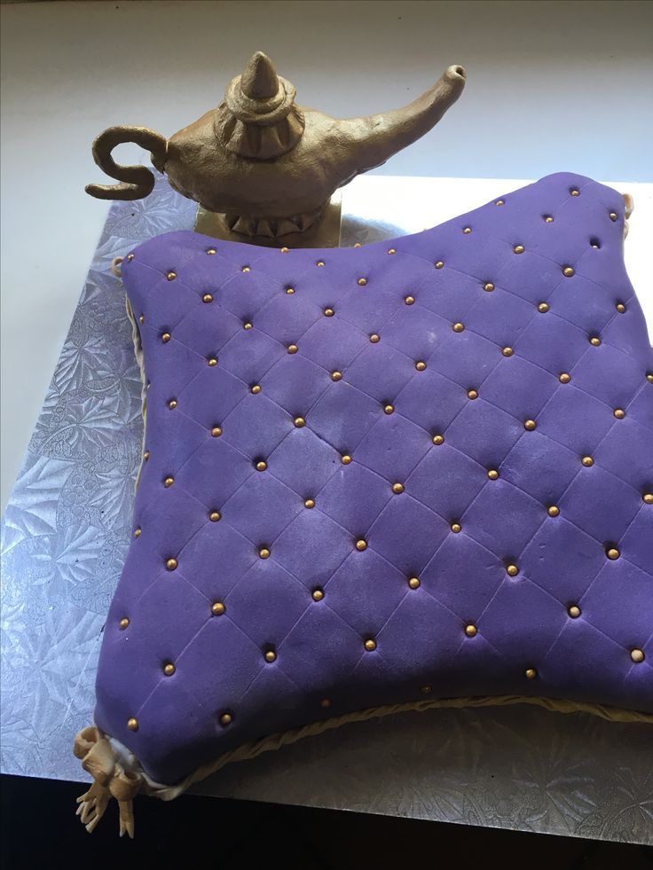 chocolate cake shaped into a pillow and covered with purple satin fondant decorated with golden dragees