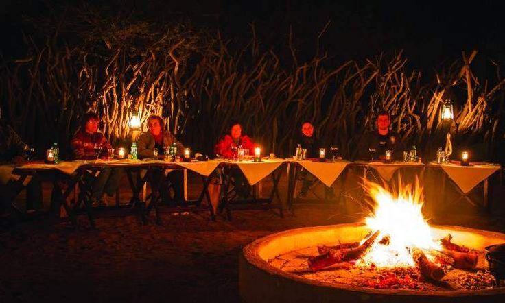 Open-air boma dinner with roaring campfire, Rhulani Safari Lodge