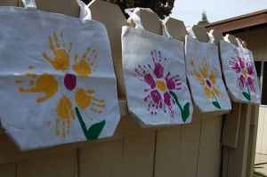 We used a smaller bag, so no room for handprints.  Instead I had the kids use just their fingers at the bottom for grass, and thumbprints for the flower petals. Then one hand print in the upper corner for the sun.  Oma loved it!
