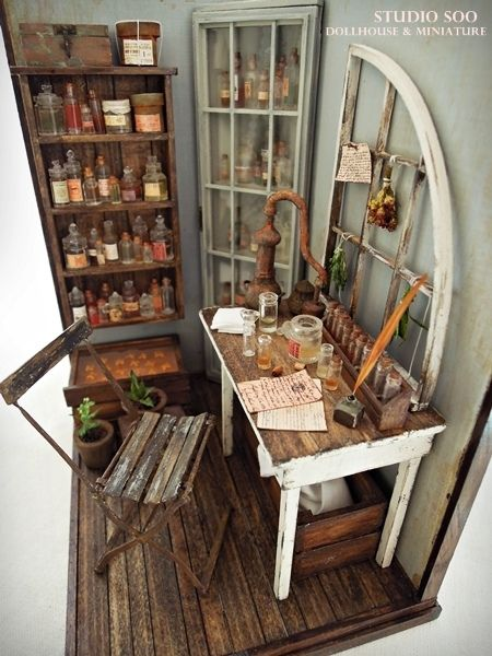 perfumer's workroom..even in this minature room they are using an old window frame on the work bench to hang things on....