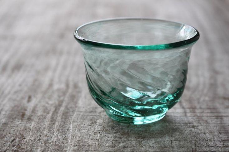 薄青のぐい呑み 徳利の口元と同じバランスに作られているぐい呑みのバランスは どんなに酔っぱらっても落とさないのでは?というほど、指がしっかりホールドされます。 指の腹部分にあたるモールが程よく気持良いお酒好きにはたまらないぐい呑みです。 熟練の技術はもとより、お酒好きの栄次さんならではのこだわりが感じられます。 また、手吹きガラスによる絶妙な気泡やガラスの筋は、さらに愛着が湧く事でしょう。 素材としてのガラスの美しさ。モールが作り出す光の屈折。 どうぞ存分にお楽しみ下さい。