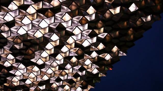 Inspired by the experience of walking through the dappled light of a forest, Canopy is a 90-metre long light sculpture spanning the front facade of the building, using mass production and precise fabrication to evoke and reflect nature. Thousands of identical modules, their form abstracted from the geometry of leaves, are organised in a non-repeating growth pattern. During the day, apertures in the modules filter natural light to the street below. After dusk, particles of artificial light…