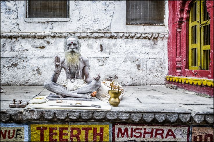 A sadhu man sitting aside in a narrow street of Varanasi. Sadhu is a holy man who has chosen to live a life apart from or on the edges of society to focus on his own spiritual practice.