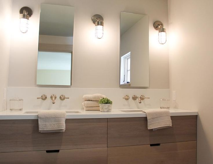 Cottage bathroom features a veneer dual washstand topped with white quartz framing his and her sinks under wall-mont faucets in a satin nickel finish and tall frameless vanity mirrors illuminated by nautical cage sconces.