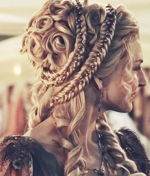 Polished curls on the crown of the head, circled by braids with inlaid pearls, few curls hanging down