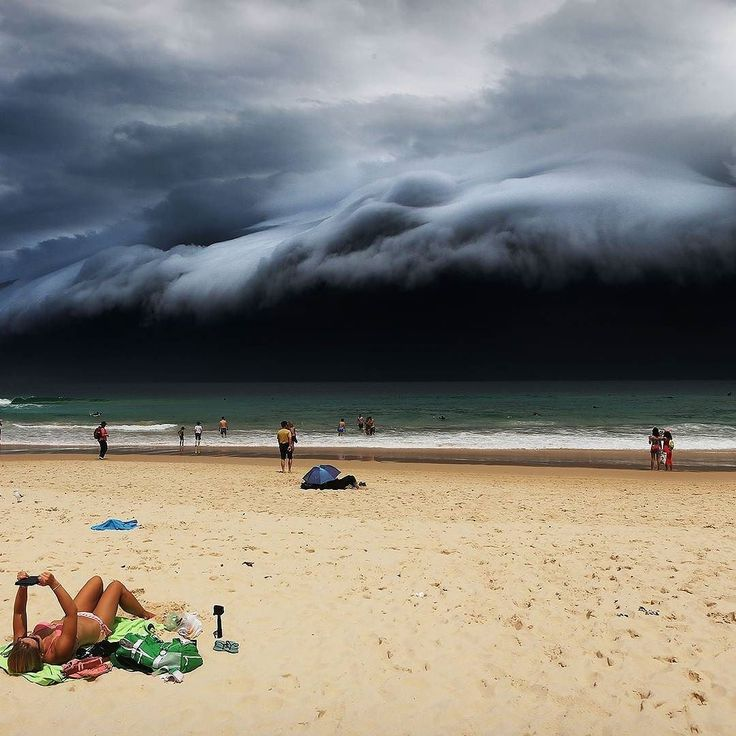 """World Press Photo first prize in the Nature Singles category: """"Storm Front on Bondi Beach"""" by Rohan Kelly for the Daily Telegraph shows a massive cloud formation looming as a sunbather reads oblivious to the approaching storm in Sydney Australia November 6th 2015. Credit: Rohan Kelly / World Press Photo via AP"""